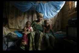 A woman sits with her children at home. Photo credits: Irene Abdou